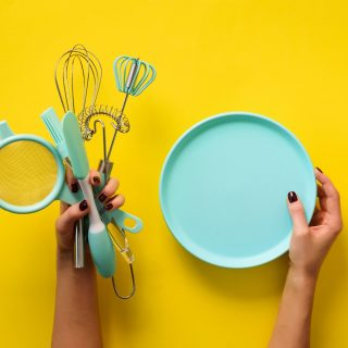Woman hand holding kitchen utensils on yellow background. Baking tools - plate, brush, whisk