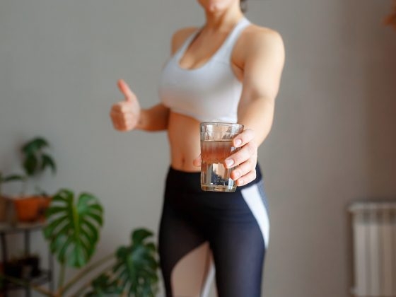 Fitness woman drinking water while training at home