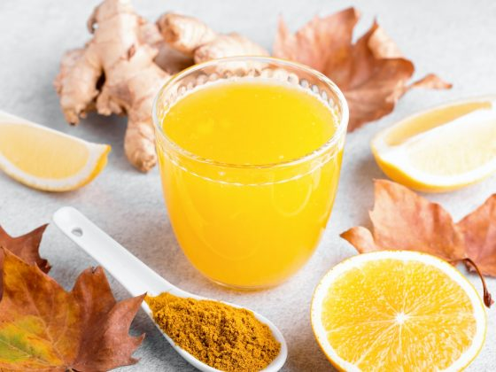 Glass of ginger smoothie with lemon and turmeric, top view