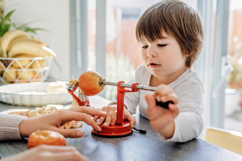 Little boy peeling apple using peeler slicer corer machine. Children making apple pie together