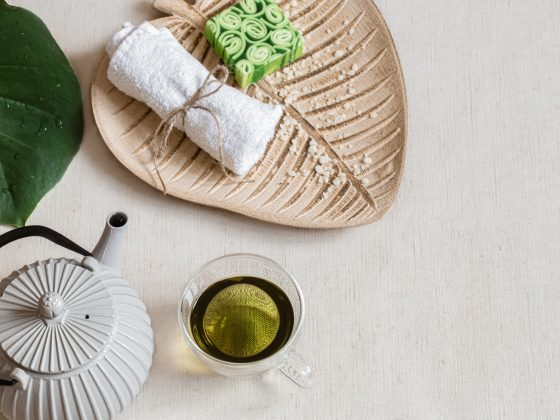 Top view spa composition with bath accessories, teapot and tea in a cup.