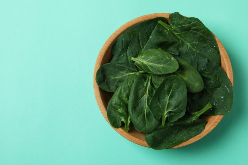 Bowl of spinach leaves on mint background
