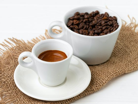 Cup of espresso coffee and coffee beans on white surface