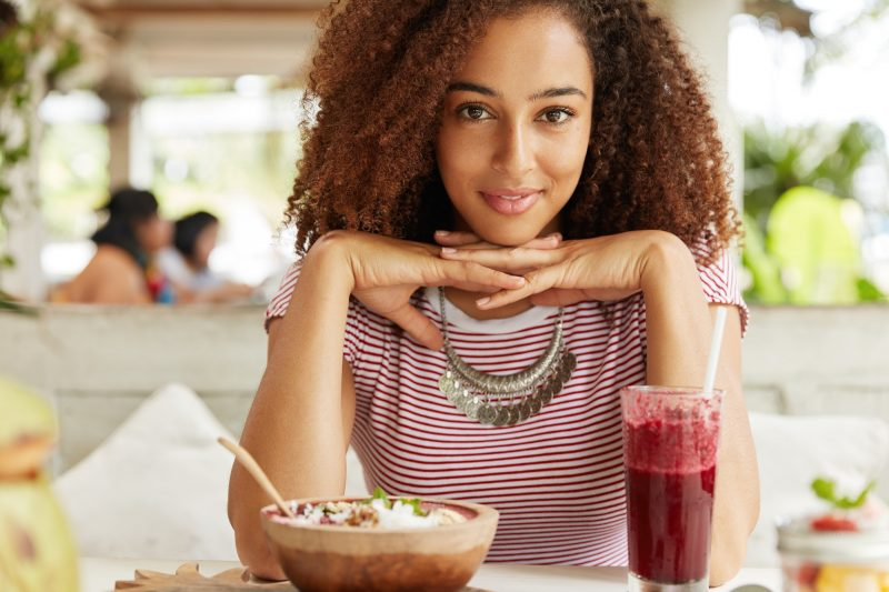 Delightful beautiful African American female student rests after lectures at university in cozy cafe