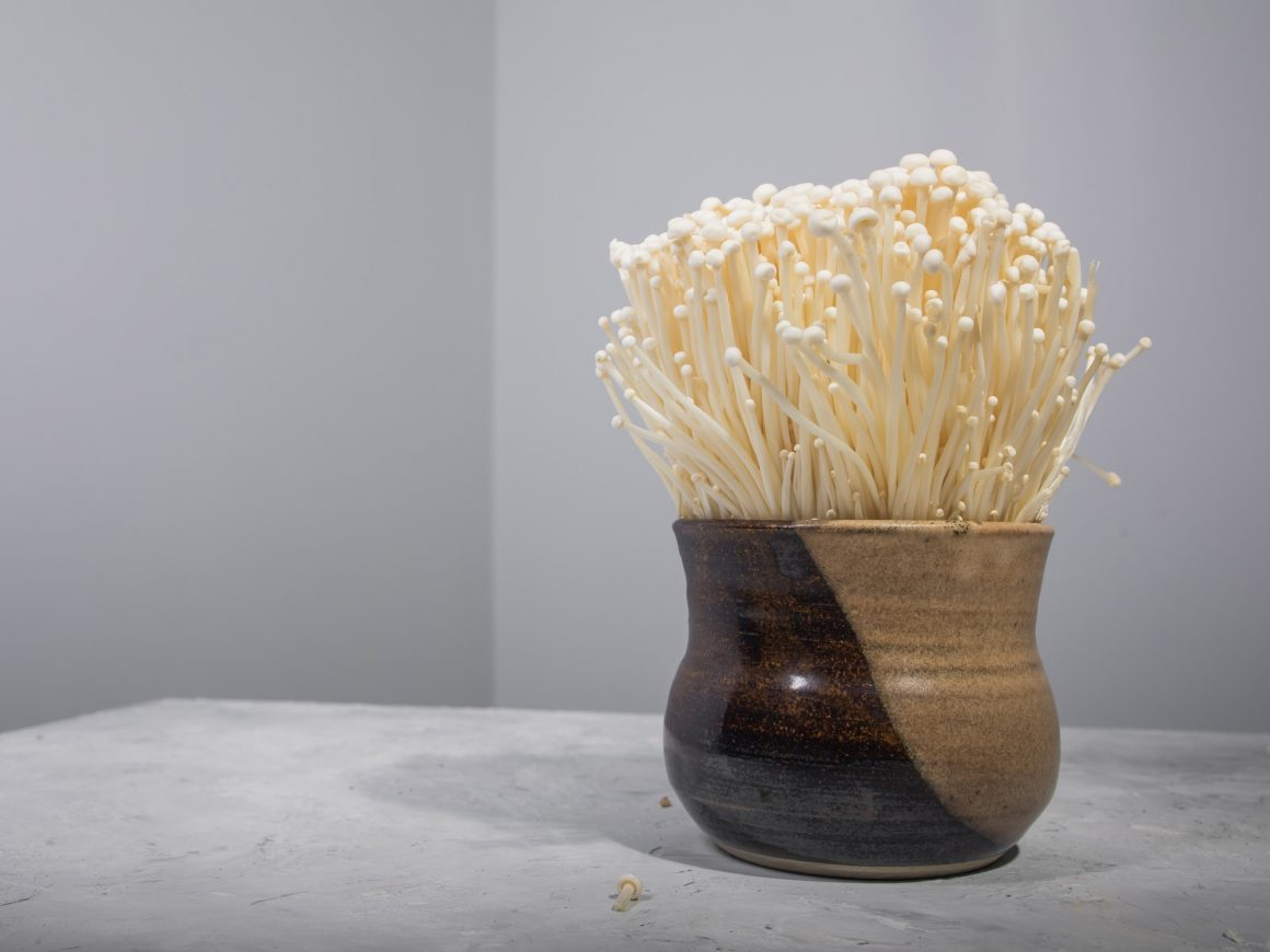 Enoki mushrooms in clay bowl on table