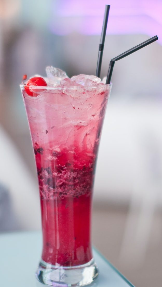 Glass of cherry soda with ice at cafe indoors