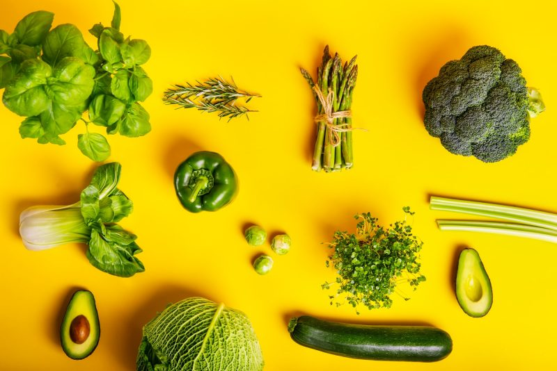 healthy raw green vegetables and greenery on the yellow background. Vegetarian and vegan diet