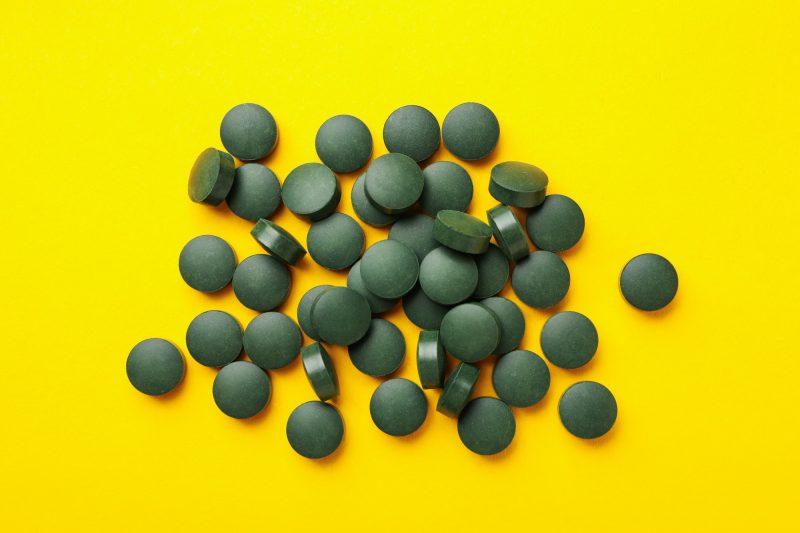 Heap of spirulina pills on yellow background, top view