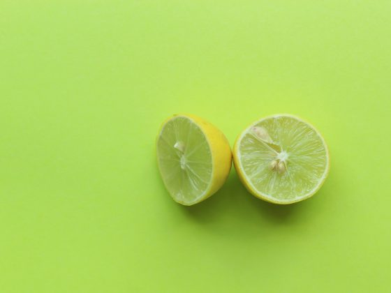 Key lime sliced in half on green background. Copy space