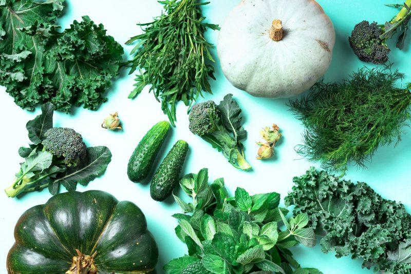 Fresh green vegetables on trendy mint background. Top view. Copy space. Clean eating, alkaline food