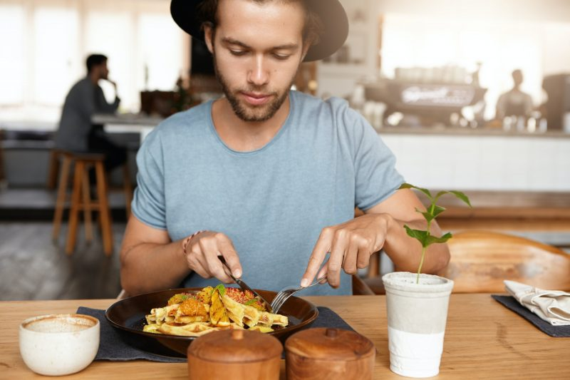 People, leisure and food concept. Close up shot of young Caucasian man in hat eating some delicious